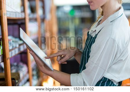 Mid-section of female staff using digital tablet in super market