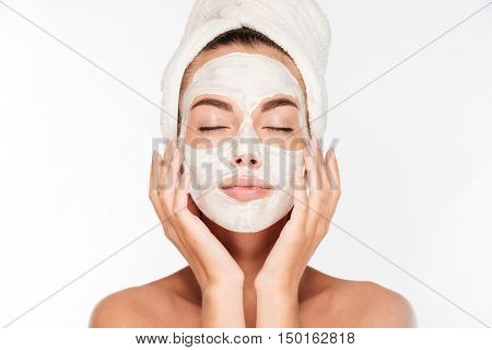 Beautiful woman with eyes closed and white clay facial mask on face isolated on white background