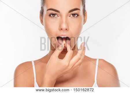 Portrait of a pretty girl with vitamin capsule on tongue isolated on white background