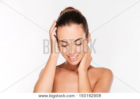 Beauty portrait of a happy woman with fresh skin looking down isolated on a white background