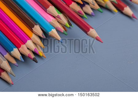 Wooden colorful pencils, on a blue wooden background