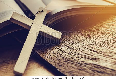 Closeup of simple wooden Christian cross necklace on Bible vintage tone god