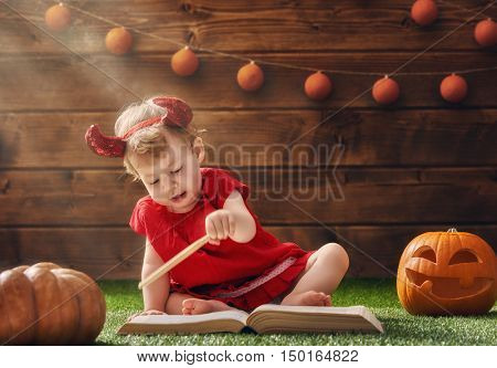 Happy Halloween! Cute cheerful little devil with a magic wand. Beautiful child baby girl in devil costume sitting on grass.