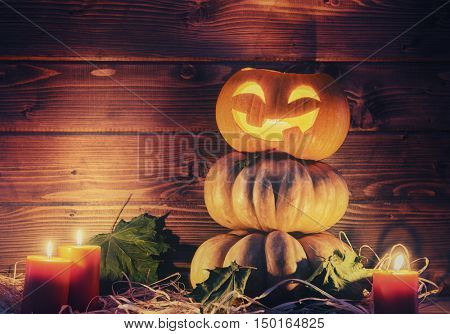 Happy halloween! Head pumpkin, candles and autumn leaves on wooden background.