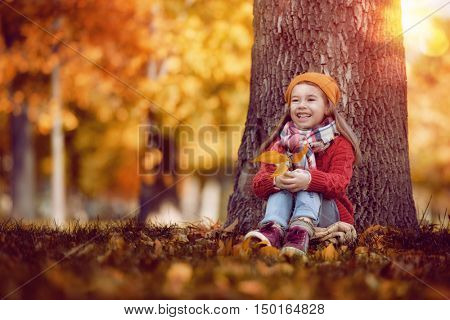 Cute little happy girl walking in autumn Park. Pretty child enjoys the beautiful autumn nature.