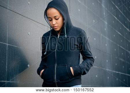 Sad and lonely teenager portrait in the city street