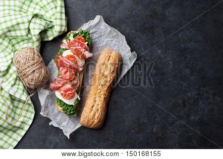 Ciabatta sandwich with romaine salad, prosciutto and mozzarella cheese over stone. Top view with copy space