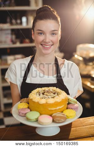 Portrait of waitress holding dessert on cake stand in cafe