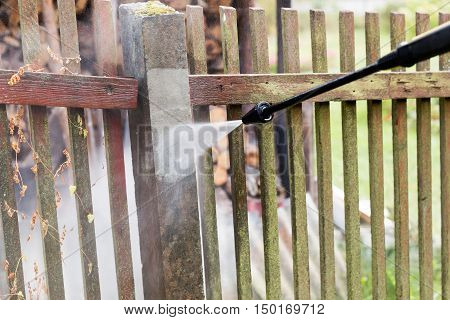 cleaning dirty garden fence post with high pressure washer