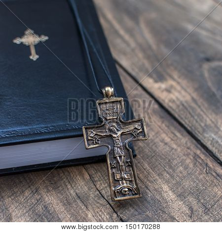 Closeup of Christian cross necklace next to holy Bible