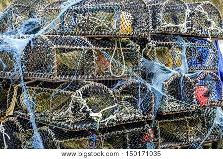 Stack of lobster pot creels on the Isle of Skye Scotland with tangled ropes and blue netting and buoys