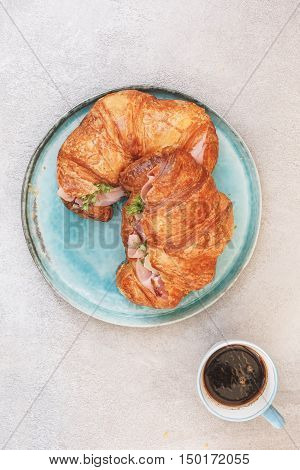 Continental breakfast with croissant on plate beside cups of coffee. Top view, blank space,retro style effect filter