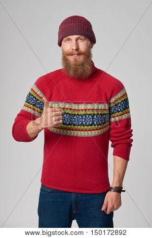 Bearded hipster man in woolen sweater and a hat looking at camera, giving thumb up gesture, studio portrait over grey background