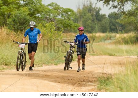 Mtb Riders Running Next To Bicycle