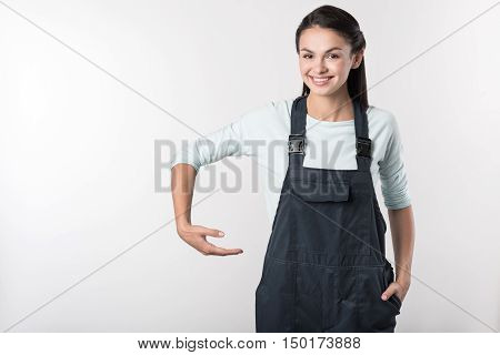 Express your true emotions. Positive delighted woman holding helmet and smiling wile standing against white background