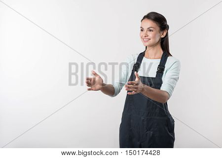 Involved in work. Pleasant diligent young woman in overalls holding her hands in front of her body and smiling while expressing joy