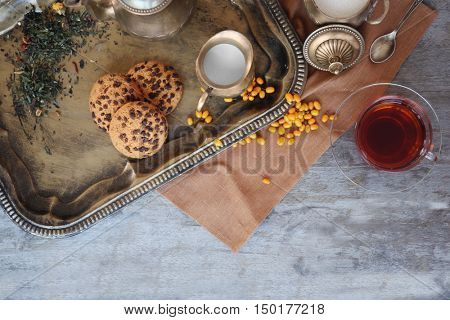 Tasty tea composition on metal tray, top view
