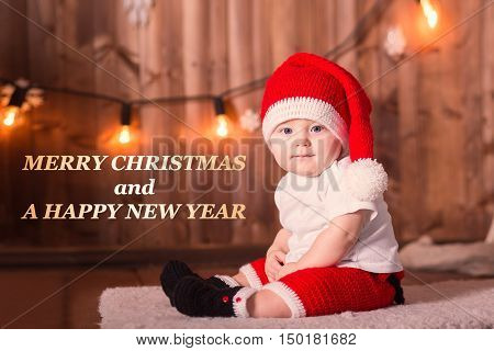 Beautiful little baby with red santa suit and hat celebrates Christmas. New Year's holidays. Baby boy in a Christmas costume smile and laught. Congratulatory text