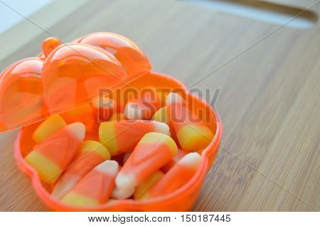 Candy corn in a clear pumpkin candy dish.