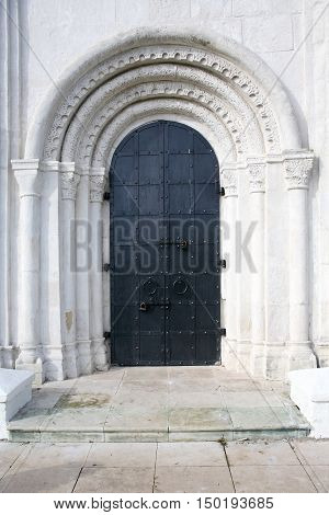 Old Russian church entrance. Arch in wall with big black metal door