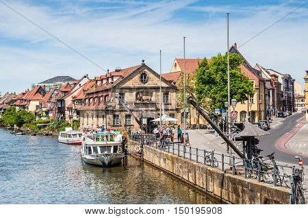 Bamberg Germany - May 22 2016: Tourist river boats and a retro derricks at Regnitz river in Bamberg. Bamberg is a UNESCO world heritage site Upper Franconia Franconia Bavaria Germany Europe.