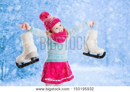 Happy laughing little girl having fun ice skating in snowy park. Winter sport and outdoor activity for family with children on Christmas vacation. Funny kid playing with snow. Child holding skates.
