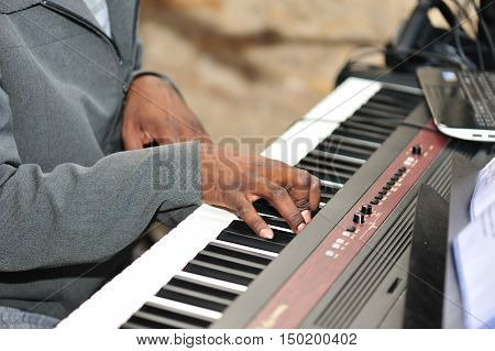 A close up image of male hands playing the piano expertly