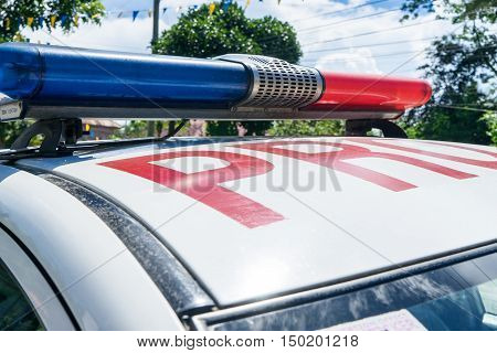 Part of philippine police car with blue and red flasher under cloudy sky at sunny day