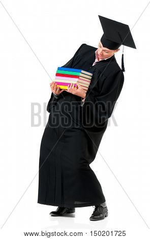 Male student carrying heavy books. Young graduation man in mantle holding stack of books isolated on white background.