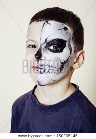 little cute boy with facepaint like skeleton to celebrate halloween emotional posing on white background