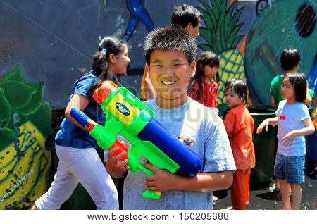 New York City - July 12 2009: Young boy with super soaker water gun at the annual Burmese Thingyan Water Festival in Chinatown