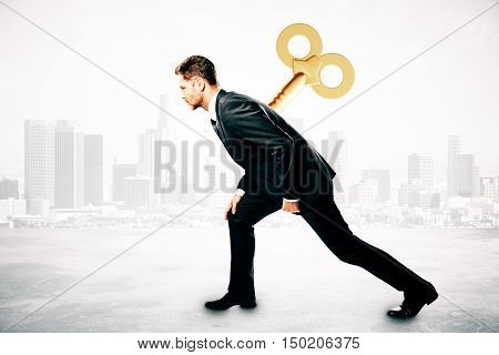 Young businessman with wind up key on his back. City background. Control concept