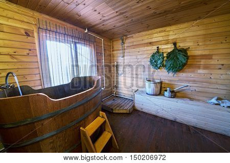 Interior of restroom in sauna with bath, shower, bench.