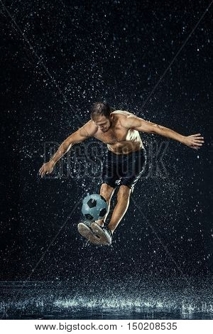 Water drops around football player on black background