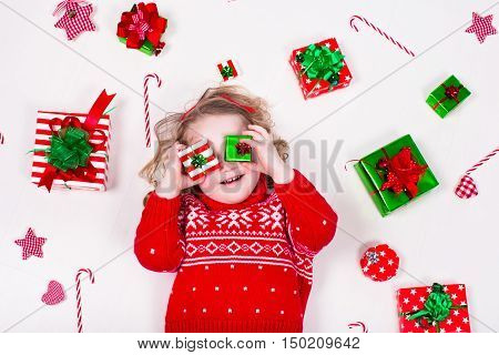 Child opening Christmas presents. Little girl in knitted winter sweater with present box. Kids open gifts. Toddler kid on the floor under decorated Xmas tree. Children play with gift box and candy.