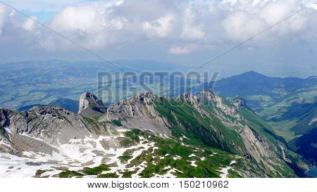 View from Saentis to steep rock faces and snow fields, in the background the foothills of the Alps in Switzerland
