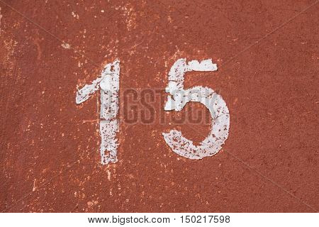 Number fifteen on the old wall of red color