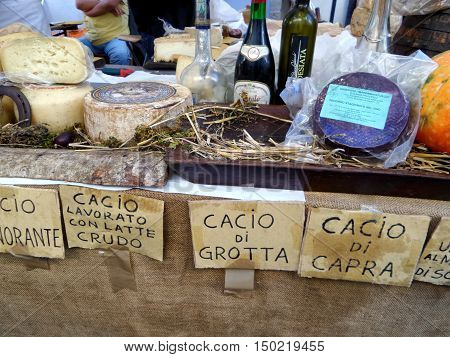 ORIOLO ROMANO, ITALY - SEPTEMBER 25, 2016: Italian cheese wines schnapps and pumpkins in sale on stand with the occasion of Porcini Mushrooms Festival.