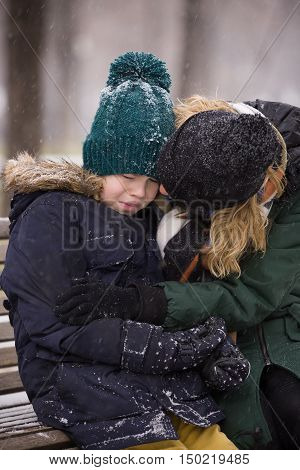 Portrait of crying kid boy sitting on a wooden bench in the park on cold day and his mother comforting and supporting him. Emotions.