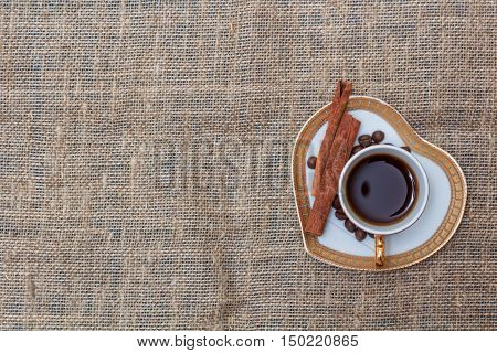 Cup black coffee on saucer in form of heart copyspace