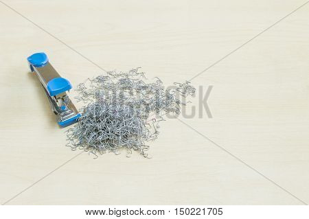 Closeup pile of used staples with blue stapler office equipment on blurred wood desk in office room textured background under window light