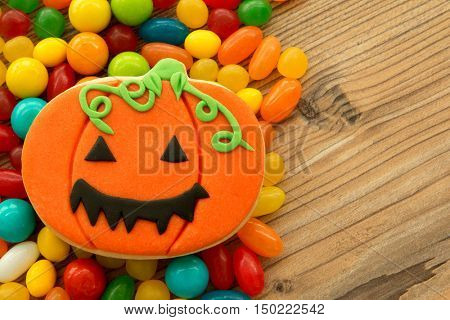 Smiling pumpkin cookie with many colorful candies on a wooden backgrund