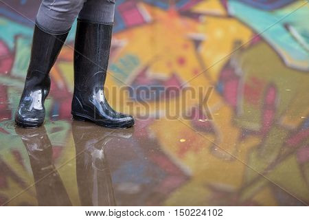 Girl in rubber boots standing in the puddle in the street. Woman in grey rubber boots splashing in a puddle after rain. Pair of grey rubber boots in a big puddle with grafiti refclections.