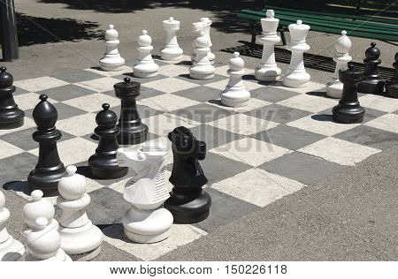 giant chess game on the asphalt, white and black figurines