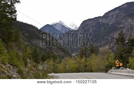 Wide view from the road on highway 99 going through the Rockies near Lillooet BC on a bright overcast day in April.