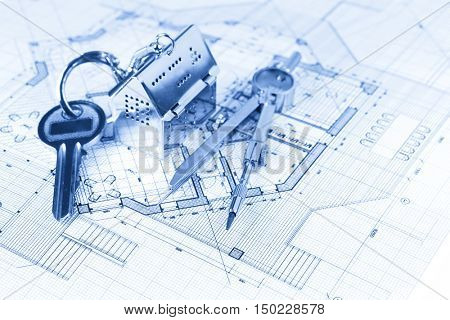 key with keychain in the form of a silver-colored house on a background of architectural drawing &  compass