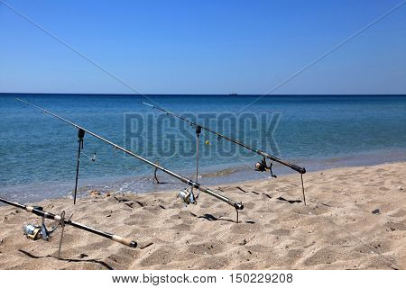Fishing rods on the beach on the seafront