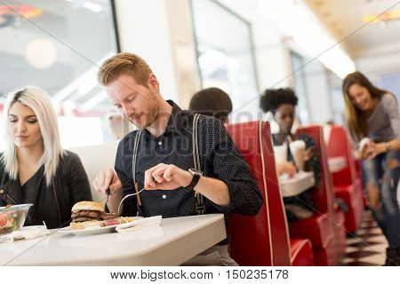 Friends eating fast food at the table in the diner