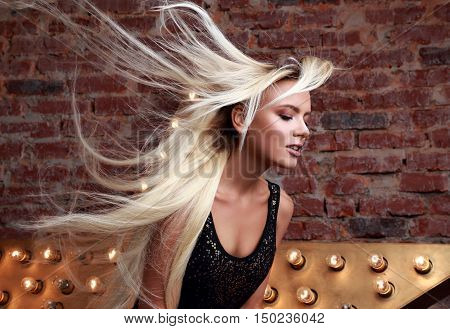 Sexy Beautiful Makeup Woman With Long Blond Streaming, Fly Away Hair Posing On Yellow Star And Brick