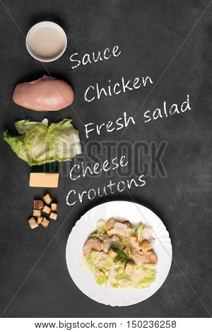 Classical Caesar salad with sliced chiken meat, fresh salad leaves, croutons and sauce in white round plate